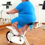 Overweight woman exercising on bike — Stock Photo