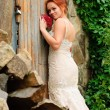 Bride near the old locked door - Stock Photo