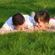 Couple lie on the grass — Stock fotografie