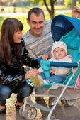 Happy family outdoor with carriage — Stock Photo