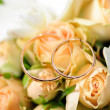 Gold rings on a bouquet of roses - Stock Photo