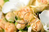 Gold rings on a bouquet of roses — Stock Photo
