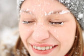 Girl's face with snow outdoors — Stockfoto