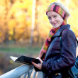 Young woman with book in autumn park — Stock Photo