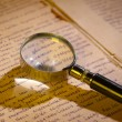Foto Stock: Magnifier glass on page of ancient manuscript