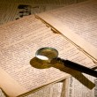 Magnifier glass on page of ancient manuscript — Stock Photo