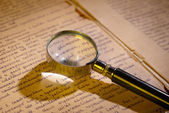 Magnifier glass on page of ancient manuscript — 图库照片