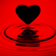 Black heart siluett over red water ripples — 图库照片