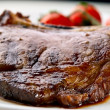 Macro of grilled meat ribs on white plate with tomatoes — Stock Photo #5085037