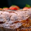 Macro of grilled meat ribs on white plate with tomatoes — Stock Photo