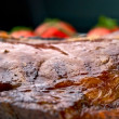 Macro of grilled meat ribs on white plate with tomatoes — Stock Photo #5144229