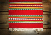 The textile traditional mat on wood backdrop — Stockfoto