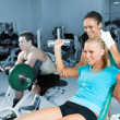 Young women lifting a dumb-bell with her trainer — Stock Photo