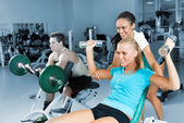 Young women lifting a dumb-bell with her trainer — Stok fotoğraf