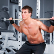 Muscular man working  with the rod — Stock Photo