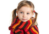 Sad little girl in a striped scarf — Stock Photo