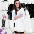 Young woman tries on a fur coat - Stock Photo