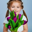 Cute little girl giving tulips - Stock Photo