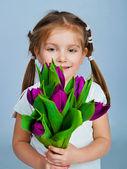 Cute little girl giving tulips — Stock Photo