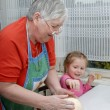 Stock Photo: Grandmother and granddaughter knead dough