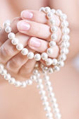 Pearls in the women's hands — Stock Photo