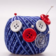 Pins in wool ball with buttons — Stock Photo