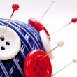 Pins in wool ball with buttons - Stock Photo