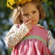 Thoughtful little girl in a dandelion wreath — Stock Photo
