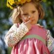 Thoughtful little girl in a dandelion wreath — Stock Photo
