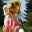 Smiling little girl in dandelion wreath — Стоковая фотография
