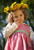 Thoughtful little girl in a dandelion wreath — Стоковое фото