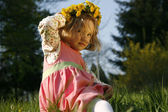 Smiling little girl in dandelion wreath — Stock Photo