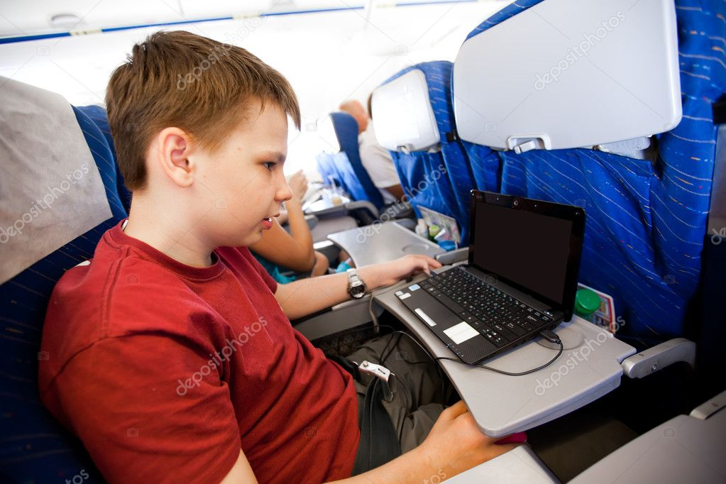 Boy flies in the plane and plays the laptop — Stock Photo #3999279