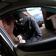 Robber and the thief in a mask hijacks the car - Stock Photo