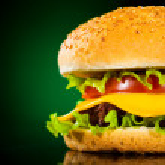 Tasty and appetizing hamburger on a darkly green — Stock Photo