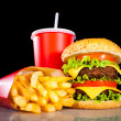 Tasty hamburger and french fries on a dark — Stock Photo
