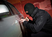 Robber and the thief in a mask hijacks the car — Stock Photo