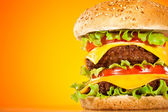 Tasty and appetizing hamburger on a yellow — Stock Photo