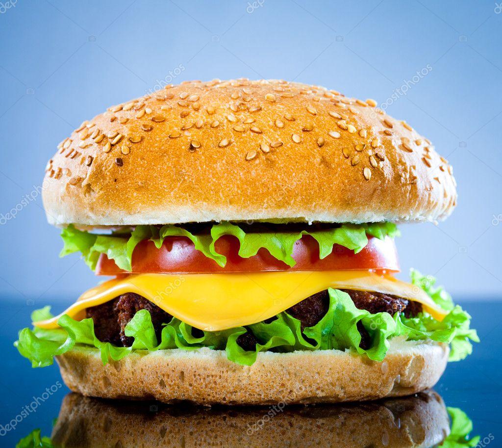 Tasty and appetizing hamburger on a blue — Stock Photo © cookelma ...