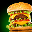 Tasty and appetizing hamburger on a darkly green - Stock Photo