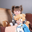 Four-year girl joyfully sits in an old suitcase — Stock Photo