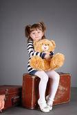 Cztery lata piękna dziewczyna siedzi na starą walizkę z zabawkami w rękach. — Zdjęcie stockowe