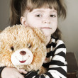 Four-year girl sits on an old suitcase with a toy bear — Stock Photo