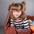 Four-year girl joyfully sits in an old suitcase - Stockfoto