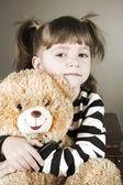 Czterech lat dziewczyna siedzi na starą walizkę z zabawkami miś — Zdjęcie stockowe
