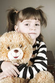 Four-year girl sits on an old suitcase with a toy bear — ストック写真