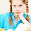 Stock Photo: Tired ten years' schoolgirl learns lessons