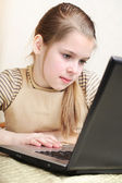 Ten years' girl works on the personal computer — Stock Photo