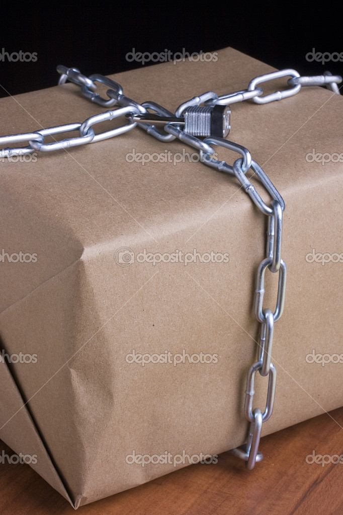 Metal chain wrapped around a box and closed with a lock. — Stock Photo #4450440