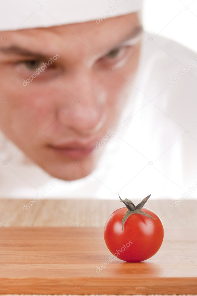 The young chef in chef's hat is considering a tomato. — Stock Photo #5174604